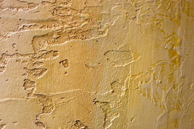 Конец-вверх красочной золотой бронзы заштукатурил неровную стену штукатурки.
