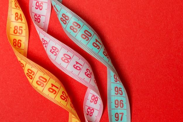 赤の背景にカラフルなメジャーテープのクローズアップ Premium写真