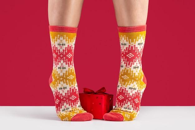 다채로운 부드러운 양말의 클로즈업입니다. 편안함과 여성 피트, 빨간색 배경의 이완의 개념. 상자에 선물.