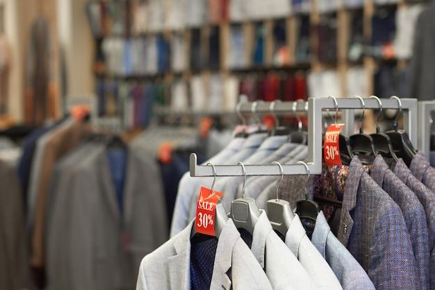 Закройте вверх красочных элегантных курток в магазине.
