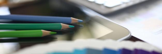 最新のデバイス上のカラフルな鉛筆のクローズアップ。オフィス詳細のマクロ撮影。仕事用の会社用品。ガジェットの黒い画面。技術とビジネスの成長の概念