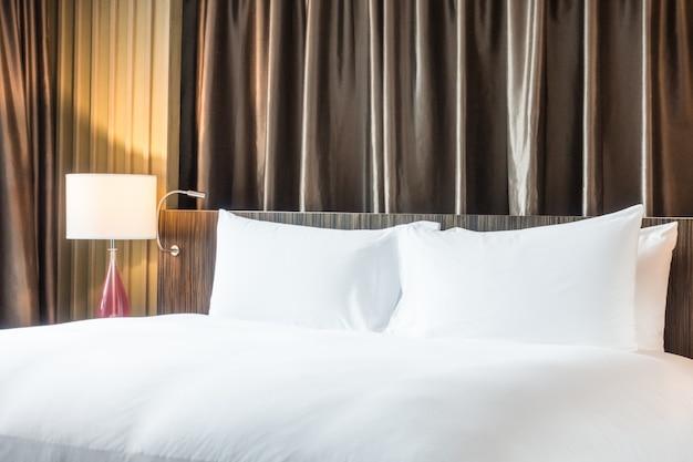 Крупный план удобной кровати с белыми простынями