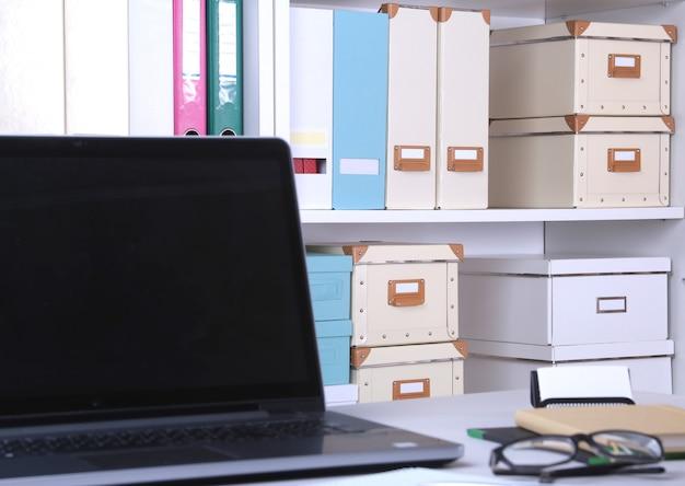 Крупный план удобного рабочего места в офисе с ноутбуком, мышью, ноутбуком, очками, ручкой и другим оборудованием, лежащим на столе на размытом фоне мебели.