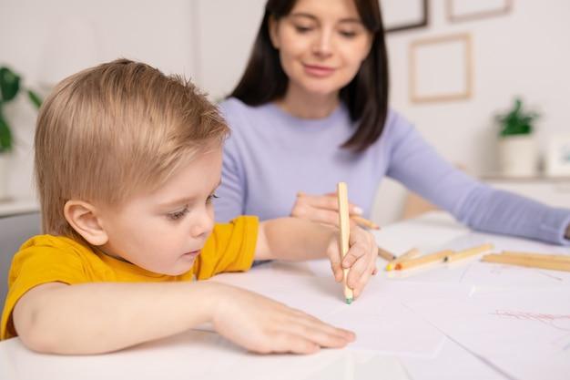 Крупный план сосредоточенного милого мальчика, сидящего за столом и использующего карандаши для рисования под контролем матери