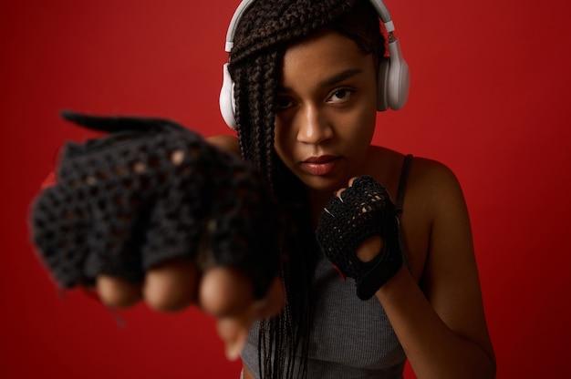 まっすぐなパンチを打つヘッドフォンと赤いボクシンググローブで集中した若いアフリカの運動女性ボクサーのクローズアップ。コピースペースで色付きの背景に分離された武道の概念に連絡してください