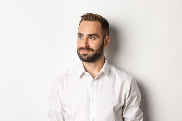 Крупный план уверенно бизнесмена в белой рубашке, смотрящего влево и довольного улыбаясь, стоя на белом фоне.