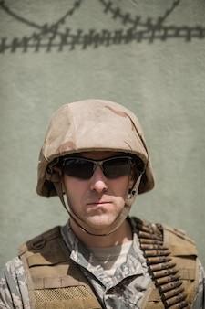 부트 캠프에서 콘크리트 벽에 서있는 자신감이 군사 군인의 근접