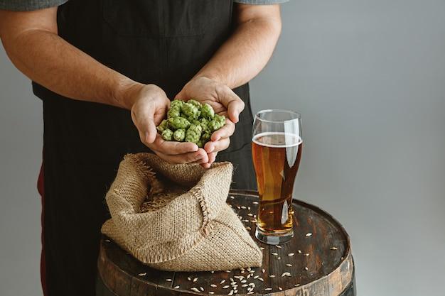 Закройте уверенно пивовара молодого человека с пивом собственного изготовления в стекле на деревянной бочке на серой стене.