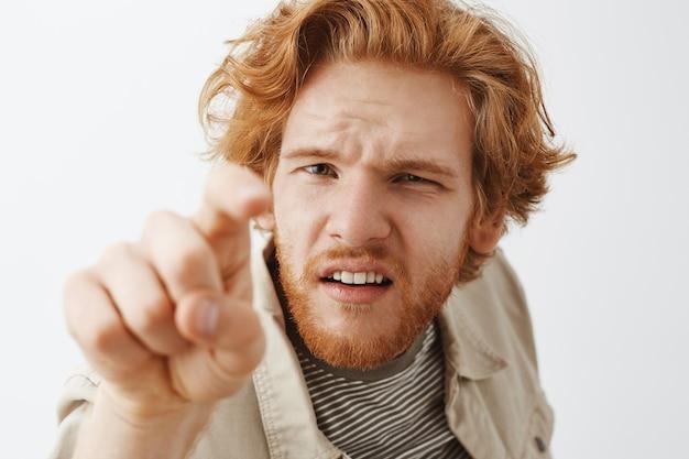 白い壁に向かってポーズをとって混乱して好奇心旺盛なひげを生やした赤毛の男のクローズアップ