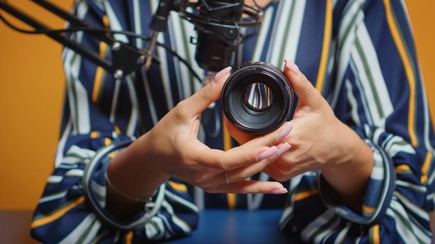 전문 스튜디오 세트에서 새 카메라 렌즈에 대한 리뷰를 작성하는 콘텐츠 작성자를 닫습니다. 온라인 인터넷 웹 쇼를 위한 비디오 사진 장비를 말하는 소셜 미디어의 뉴 미디어 스타 인플루언서