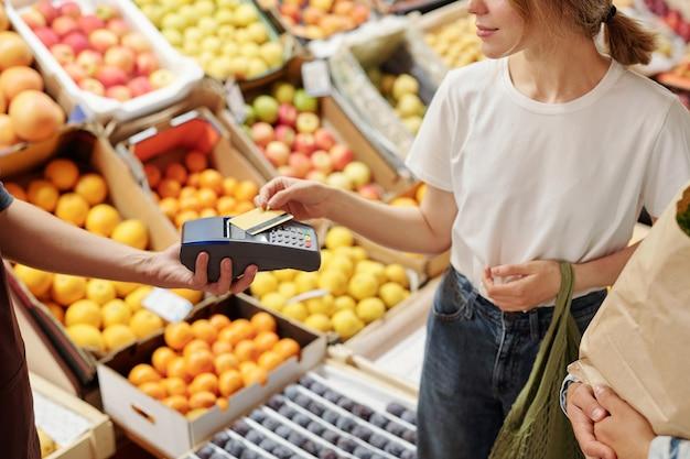 Крупный план довольной молодой женщины, платящей за органические продукты с помощью беспроводной карты на фермерском рынке