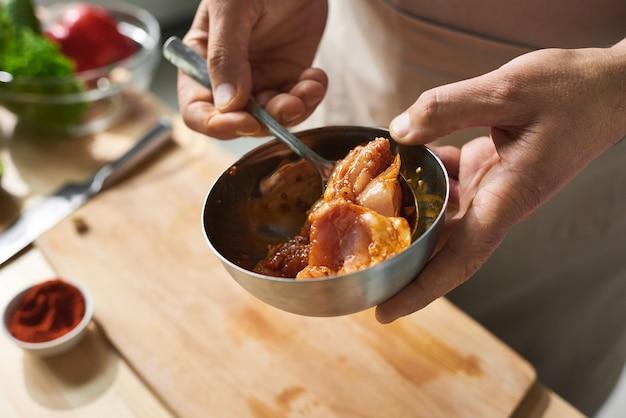 Крупный план повара, держащего миску, он готовит куриное мясо с соевым соусом