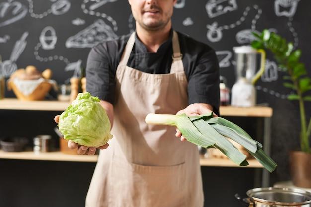 Крупный план повара в фартуке показывает свежие овощи в руках, стоящих на кухне