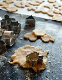 暗いテーブルの生地のクッキーカッターのクローズアップ