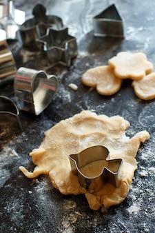 暗いテーブルの上のクッキーカッターのクローズアップ Premium写真