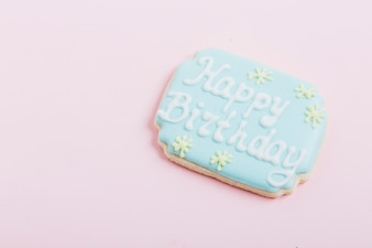 Close-up of cookie with happy birthday text over pink backdrop