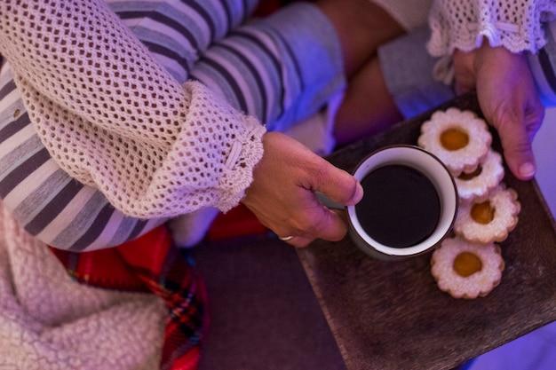 木の板の上のクッキーとコーヒーのクローズアップ-ソファやベッドに一人で座っている冬の女性の寒い日クリスマスの日