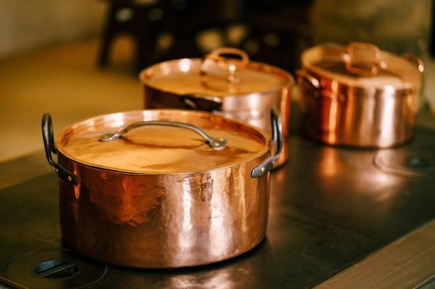 アンティークバーナーストーブの閉じた蓋付きの銅製ポットのクローズアップ