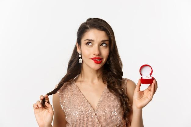Крупный план кокетливой красивой женщины, думающей о браке, держащей обручальное кольцо и смотрящей в верхний левый угол, глупо улыбаясь, на белом фоне.