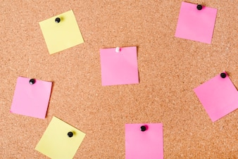 Close-up of corkboard with various note papers