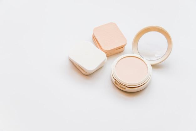 白い背景にスポンジで化粧品の現実的なプラスチック製コンパクトパウダーのクローズアップ