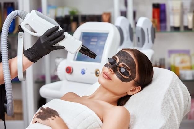 Крупный план руки косметолога, работающей над женским лицом с помощью лазерной машины красоты, косметическая терапия в салоне красоты от профессионального апарата