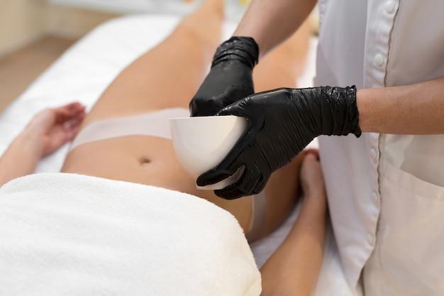 Крупный план косметолога, делающего антицеллюлитный массаж и пилинг живота солью молодой женщине в спа. концепция ухода за кожей и телом.
