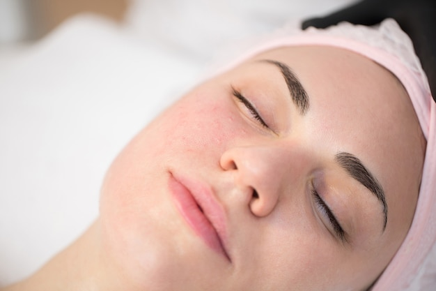 美容師のクローズアップは、美容クリニックで女性の顔の皮膚を引き締めるための若返りの顔の注射手順を行います。