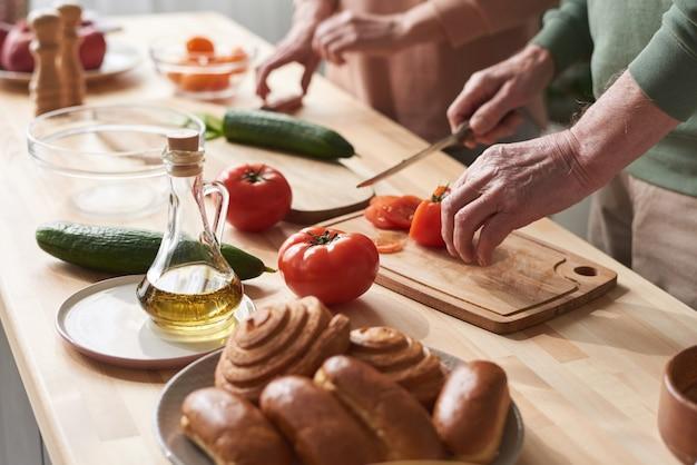 彼らが台所のテーブルでサラダを準備しているまな板の上で新鮮な野菜を切るカップルのクローズアップ