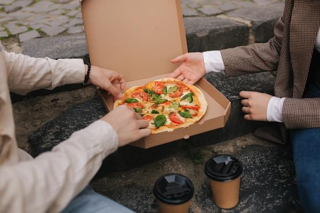 カップルのクローズアップは、屋外でボックスからピザのスライスをつかみます