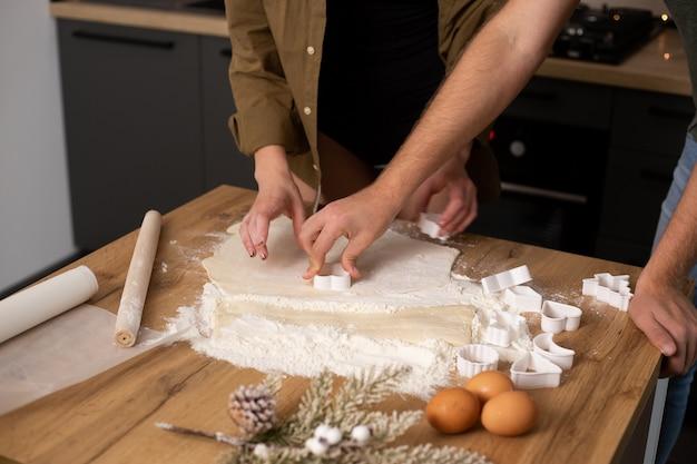 キッチンでクッキーを調理するカップルの手のクローズアップ