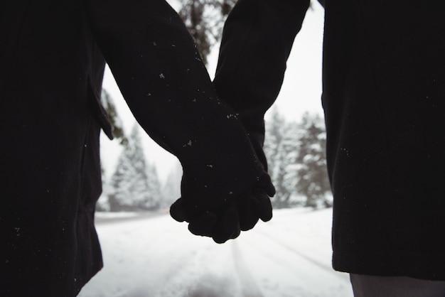 冬の間に森で手をつないでいるカップルのクローズアップ