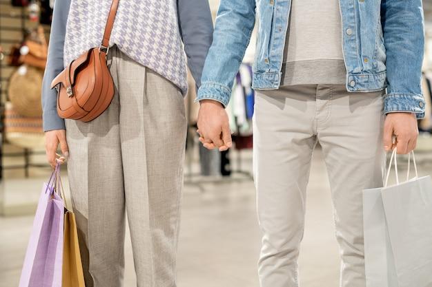 ショッピングモールで一緒に買い物をしながら手をつないでいるカップルのクローズアップ