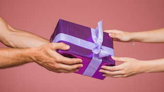 Close-up of couple holding wrapped purple gift box against colored background