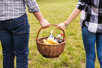 Close-up of couple's hand holding picnic basket in the park