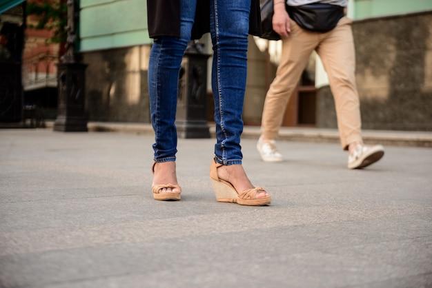 通りを歩いてケッズでカップルの足のクローズアップ。
