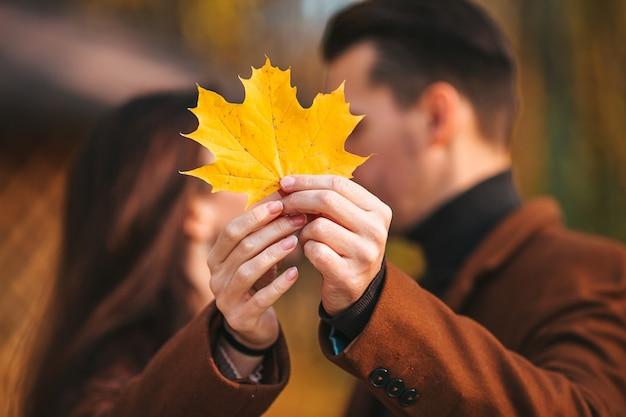 Закройте пару с желтым кленовым листом, целуя в осеннем парке. счастливая семья из двух человек осенью