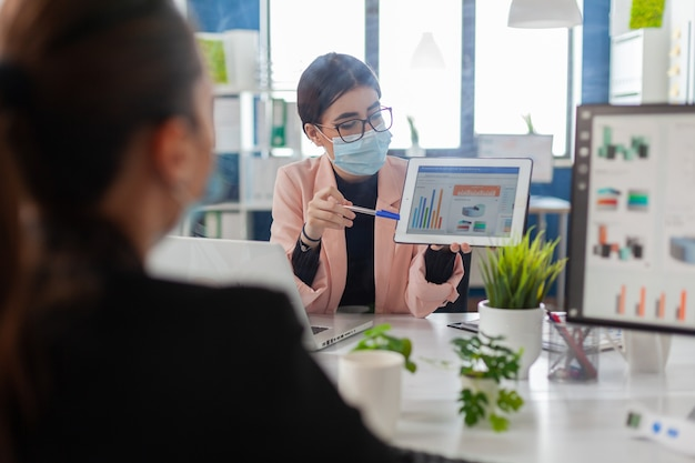 회사 사무실에 앉아 태블릿 컴퓨터를 사용하여 금융 프로젝트에서 함께 일하는 얼굴 마스크를 쓴 동료들. 팀은 covid19 감염을 피하기 위해 사회적 거리를 유지합니다.