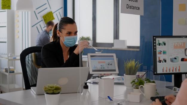 Закройте коллег с маской для лица, работающих вместе над финансовым проектом с помощью планшетного компьютера, сидя в офисе компании. команда поддерживает социальную дистанцию, чтобы избежать заражения covid19