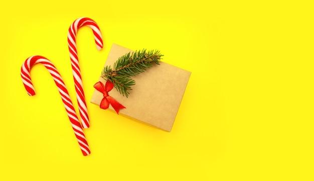 赤い弓、モミの枝、お菓子のクラフトギフトボックスのクローズアップは、コピースペースと黄色の背景にあります。
