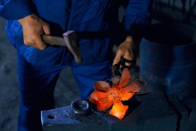 アンビルに溶融金属を鍛造する職人のクローズアップ