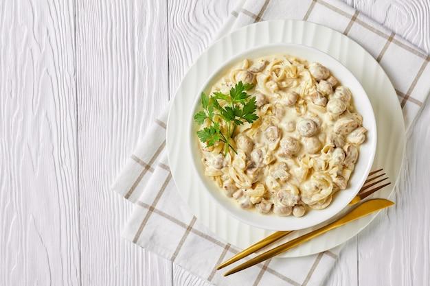 Крупный план сливочного грибного соуса, обжаренные в сметанном соусе шампиньоны в миске на белом деревянном столе, горизонтальный вид сверху