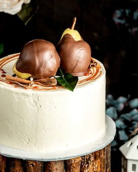 Крупным планом сливочный пирог с шоколадом грушей и палочкой корицы