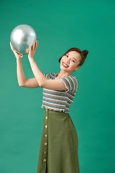 手で風船を持って、パーティーで踊ったり祝ったりする創造性のある女性のクローズアップ