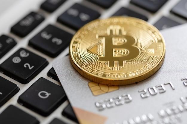 コンピューターのキーボードのクレジットカードとビットコインのクローズアップ