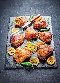 Крупный план хрустящих жареных куриных бедер с обжаренными ломтиками лимона, перцем халапеньо и тимьяном на черном каменном подносе на бетонном столе, вид сверху