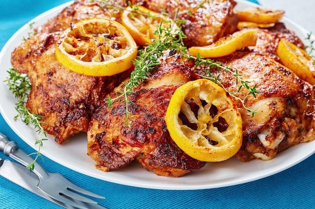 Крупный план хрустящих жареных сочных куриных бедер с обжаренными ломтиками лимона на белой тарелке на бетонном столе с греческим салатом в миске, вид сверху