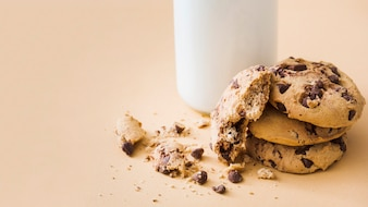 Close-up of crushed chocolate cookies with milk bottle on beige background