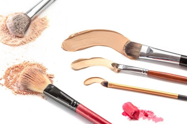 Крупный план измельченного минерального пудра мерцающего золотистого цвета с кисточкой для макияжа