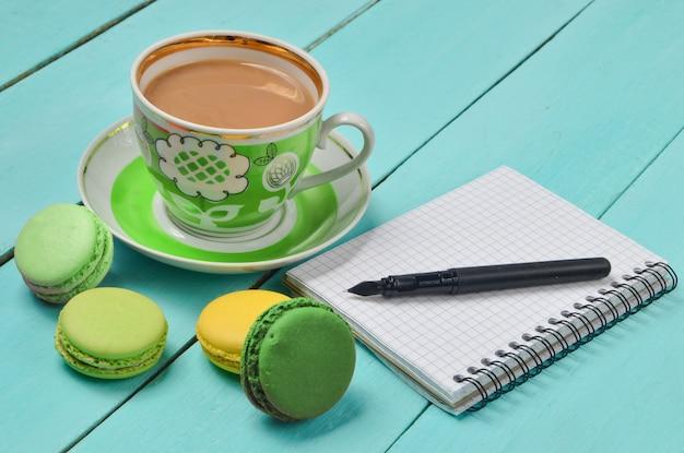 カラフルなマカロンとメモ帳とコーヒーのカップのクローズアップ